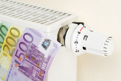 Waste of Heating costs. Close-up of a heating with thermostat in full position and euro banknotes on the side Royalty Free Stock Image