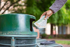 Waste of money. Closeup cropped portrait of someone hand tossing cash dollar bills money, hundred dollar bills in trash can, isolated outdoors green trees Royalty Free Stock Photography