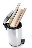 Waste paper bin filled with books. Cylindrical metal waste paper bin filled with hardcover books possibly from a student venting his or her frustration with the Stock Photos