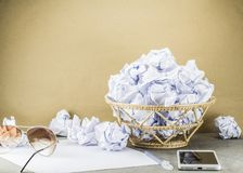 Waste paper in bin is overflow on work table. Stock Photo