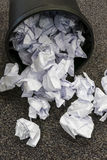 Waste paper bin tipped over and paper spilled out Royalty Free Stock Image
