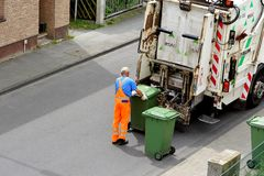 The waste paper collector uploads green containers in a truck. The waste paper collector prepares to unload green containers in a truck. Germany Royalty Free Stock Photos