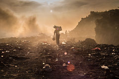 A waste picker. Is collecting reusable or recyclable materials in a open burning dump Stock Images
