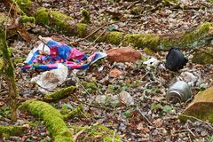 Waste plastic and glass bottles, packages and other types of waste at illegal landfill in park. Environment pollution stock image