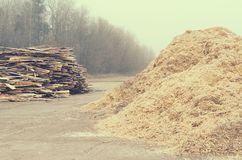 Waste sawmill in the form of a stack of boards and a mountain of sawdust. Waste sawmill in the form of a stack of boards and a mountain of sawdust Stock Images