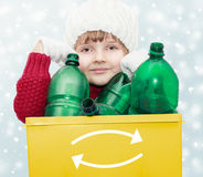 Waste sorting theme. Cute young girl with plastic bottles in recycle bin on winter background - waste sorting theme Royalty Free Stock Photos