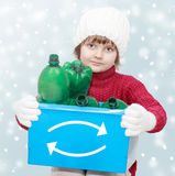Waste sorting theme. Cute young girl with plastic bottles in recycle bin on winter background - waste sorting theme Royalty Free Stock Image