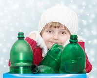 Waste sorting theme. Cute young girl with plastic bottles on winter background - waste sorting theme Stock Images