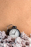 Waste time concept. Alarm clock with trash paper stock photography