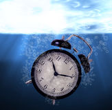 Waste of Time Concept. Drowning alarm clock royalty free stock image