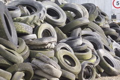 Waste tyre stack. Waste tyres piled up on a farm in England. The tyres are going green with mould and lichen and are a mixture of car truck and tractor origins Stock Photography