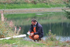 Waste water Technician. The tech is taking samples to be tested at a lab after Stock Photo