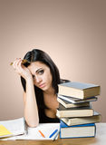 Wasted. Wasted, portrait of an exhausted young student with pile of books Royalty Free Stock Image