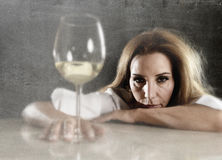 Wasted alcoholic woman depressed looking thoughtful with white wine glass Royalty Free Stock Photos