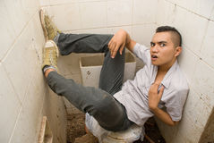 Wasted Asian punker. Desperate young male Asian emo punker hanging wasted and with a hopeless expression in a vandalized urban small washroom or lavatory, floor stock photo