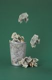 Wasted money - Dollar bills. Photo of a waste basket full of money - some bills are just dropped in the basket Royalty Free Stock Photography