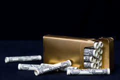 Wasteful Habit - Concept Smoking. Pack of cigarettes (Rolled dollar bills) symbolic of expensive bad habit Royalty Free Stock Photography