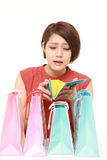 Wasteful Japanese woman with empty wallet. Studio shot of young Japanese woman on white background Royalty Free Stock Images