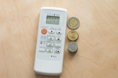 Wasteful spending air condition remote with coin, Top view Royalty Free Stock Photo