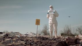 Wastes of human life, woman in uniform and protective glasses holding poster think green standing at landfill in boots stock video