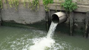 Wastewater flow down from sewer pipe pollutes city river