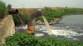 Wastewater from two large rusty pipes merge into the river