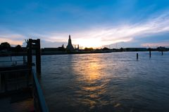 Wat Arun, κατά μήκος της πλευράς ποταμών Chao Phraya με έναν ζωηρόχρωμο ουρανό Στοκ Φωτογραφία