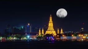 Wat Arun вечером со светлым золотом самый старый висок Chao Рекы Phraya и полнолуния в темном небе двигая вверх быстро сток-видео