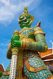 Wat Arun, Bangkok - photo of one the temple`s gates with the gigantic guardians protecting it. Background royalty free stock photos