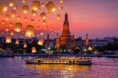 Wat arun and cruise ship in night time and floating lamp in yee peng festival under loy krathong day. Bangkok city ,Thailand stock images