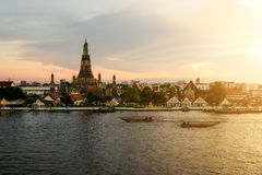 Wat Arun during sunset woth longtail boat in Chao Phraya river a. T Bangkok city ,Thailand Stock Photos