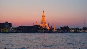 Wat Arun-tempel en Chao Phraya-rivier in Bangkok tijdens zonsondergang wordt verlicht die stock footage