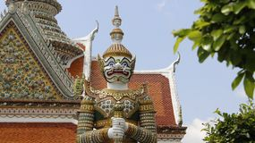 Wat Arun Temple And Giant Guarding With Colorful Mosaic. Wat Arun Temple With tiles roof and titan gatekeeper  decoration with colorful mosaic in Bangkok Stock Images