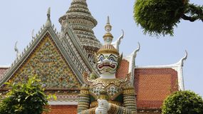 Wat Arun Temple And Giant Guarding. Wat Arun Temple With tiles roof and titan gatekeeper  decoration with colorful mosaic in Bangkok Thailand Stock Image