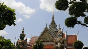 Wat Arun Temple And Giants Guarding. Wat Arun Temple With Mosaic tiles roof and titan gatekeeper  decoration with colorful mosaic Flowers in Bangkok Thailand Stock Image