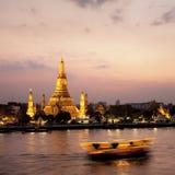 Wat Arun a través del río de Chao Phraya durante puesta del sol foto de archivo