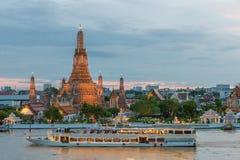 Wat Arun y barco de cruceros en noche, ciudad de Bangkok, Tailandia Fotografía de archivo