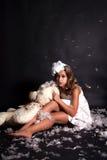 Wat betreft een meisje-engel met een beer en vliegende veren. Stock Foto's
