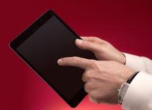 Wat betreft een tablet op rood Stock Foto's