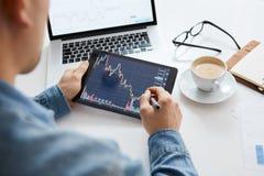 Wat betreft effectenbeursgrafiek op een apparaat van het aanrakingsscherm Handel op effectenbeursconcept stock afbeeldingen