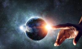 Wat betreft planeet met vinger royalty-vrije stock afbeelding