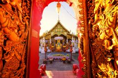 Wat Ming Muang at sunset, Chiang Rai. Red golden gate entrance of Wat Ming Muang against sunset light in Chiang Rai, Thailand. Traditional Lanna Thai temple stock photography