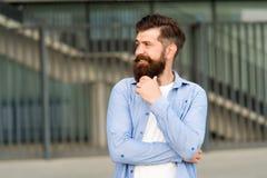 Wat op zijn mening is Peinzende hipster die prettige gedachten denken Stedelijke achtergrond van mensen de gebaarde hipster Regel stock foto