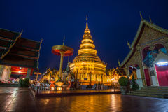 Wat Phra That Hariphunchai i skymningtid Arkivbild
