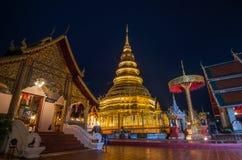 Wat Phra That Hariphunchai i skymningtid Royaltyfri Bild