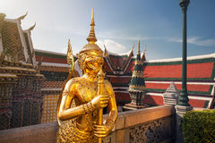 Wat Phra Kaew in Bangkok at sunset. Golden Guardian Statue in the Temple of the Emerald Buddha Wat Phra Kaew in Bangkok at sunset royalty free stock image