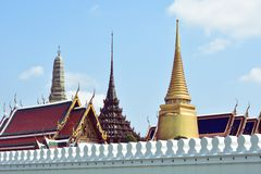Wat Phra Kaew behind white wall and blue sky in background stock photo