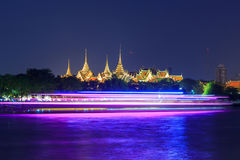 Wat phra kaew with blur light of boat moving passed Stock Photos