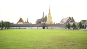 Wat Phra Kaew, Grand palace, Temple of the Emerald Buddha with sky and green lawn. Landmark of Bangkok,Thailand stock video footage