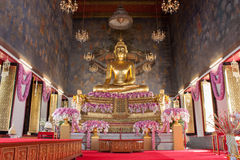 Wat Ratchanaddaram Buddha. Statue of Buddha in the Radnudda temple church with rarely special decoration with purple flowers for  Queen Sirikit welcome Royalty Free Stock Photo